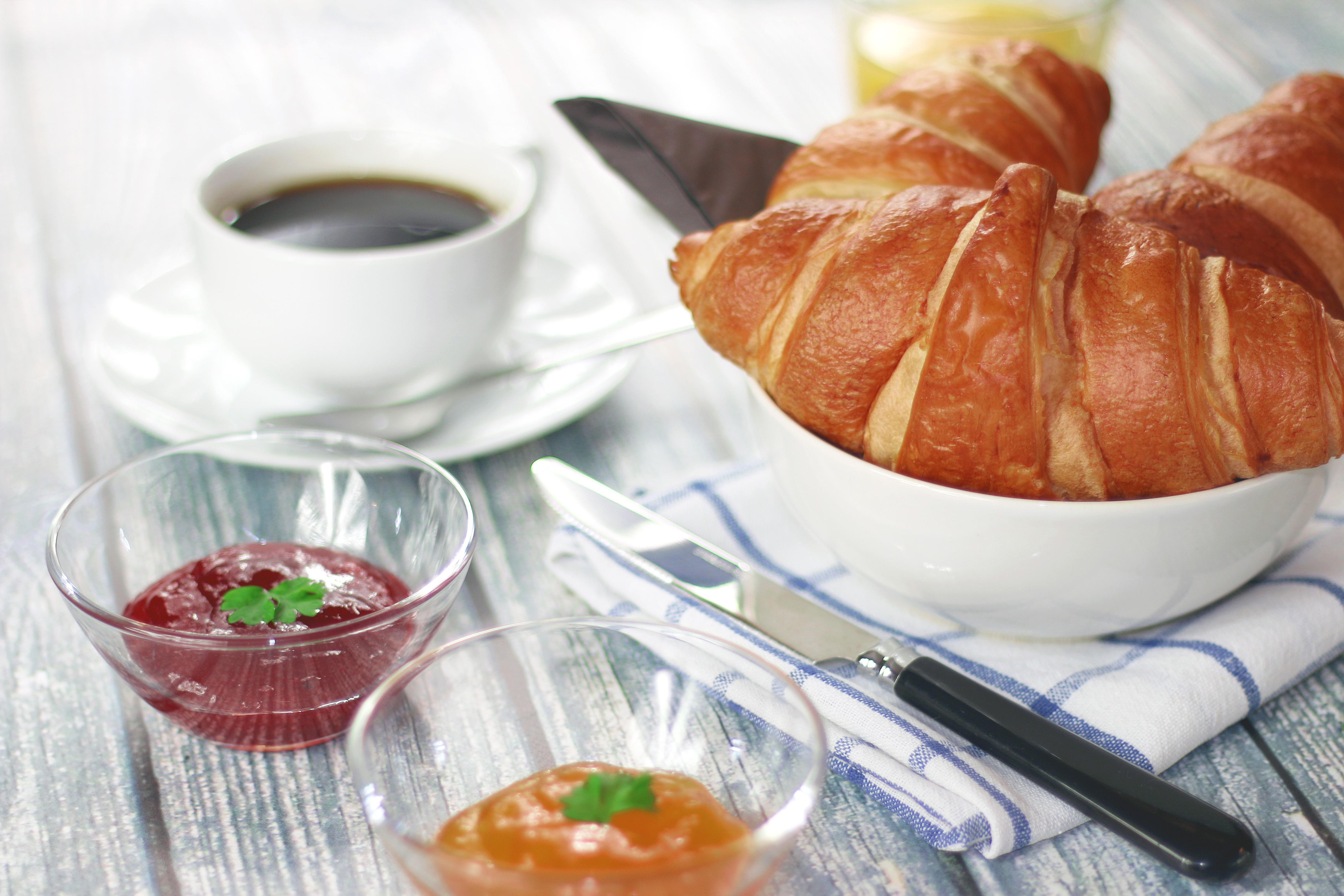 Frühstückstisch mit Kaffee, Croissant und Marmelade, wie er beim Arbeitsfrühstück aussehen könnte